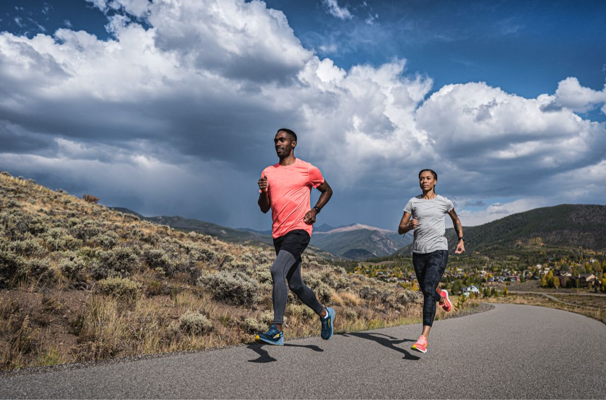 A man in gray tights and a orange shirt and a woman in grey tights and a green shirt running on a path in the new Torin 5.